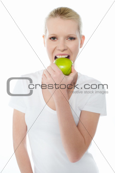 Healthy young girl eating nutritious green apple