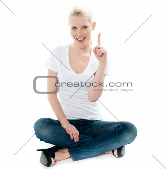 Cute young girl seated on floor and pointing up