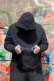 Man in handcuffs on a wall background