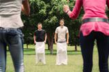 men playing sack race with girlfriends cheering