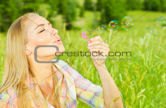 Pretty woman blowing soap bubbles in park