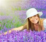 Beautiful happy female lying down on lavender field