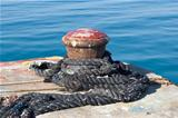 Old rusty mooring bollard on pier