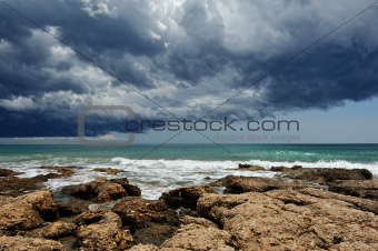 Sea landscape with rocky coast and storm sky .