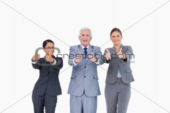 Three businesspeople giving thumbs up