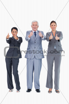 Three smiling businesspeople giving thumbs up