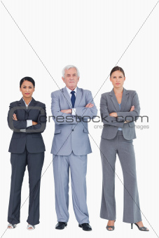 Three businesspeople with arms folded
