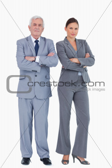 Mature businessman and colleague with arms folded