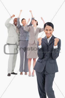 Successful saleswoman with cheering team behind her