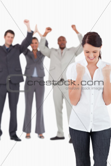 Triumphant businesswoman with cheering colleagues behind her