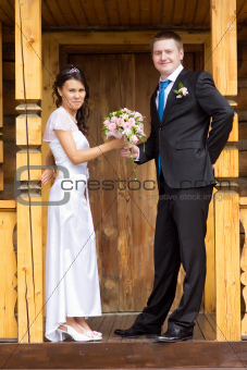 The bride and groom with a bouquet in a wooden porch