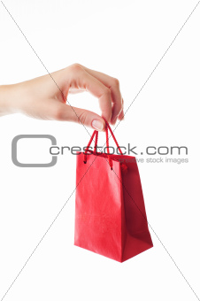 female hand holding red gift bag with present with her fingers -