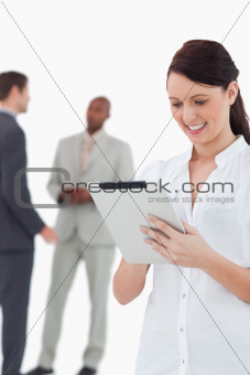 Saleswoman with tablet and associates behind her