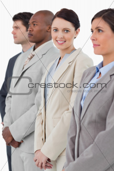 Smiling businesswoman standing between her associates