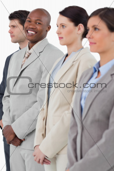Smiling businessman standing between his associates