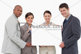 Smiling businessteam holding blank sign together