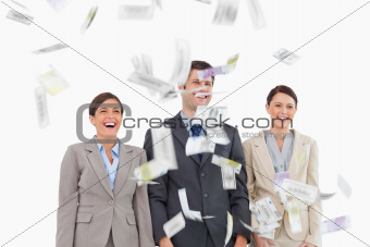 Money dropping down on smiling businessteam