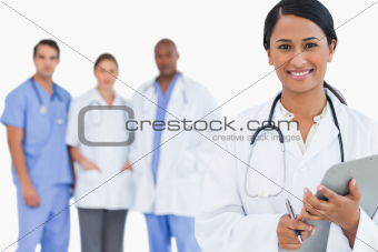 Smiling doctor with clipboard and members of staff behind her