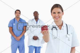 Doctor offering apple with colleagues behind her