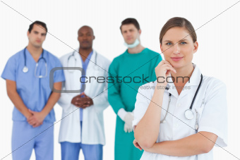 Thoughtful doctor with male colleagues behind her