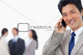 Smiling businessman on mobile phone and team behind him