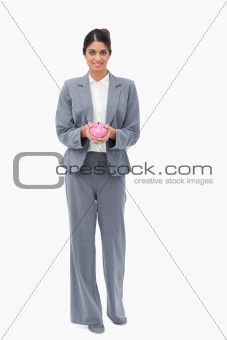 Smiling bank employee with piggy bank in her hands