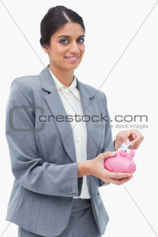 Smiling bank assistant putting money into piggy bank