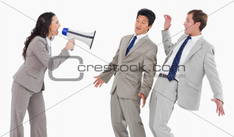 Businesswoman with megaphone shouting at colleagues