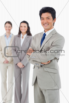 Confident smiling businessman with his employees behind him