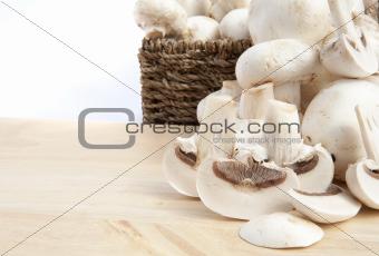 Fresh champignon mushrooms in rustic basket isolated on white