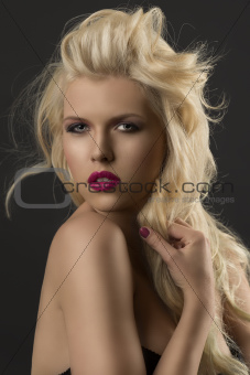 beauty portrait of blonde girl she touches a lock of hair