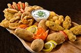 Rustic tray with various meats, cheese balls and garlic sauce- isolated