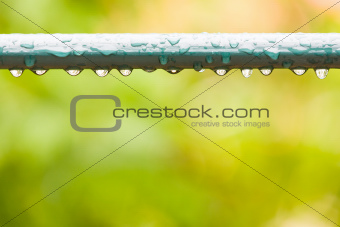 Raindrops on a fence in city park or garden