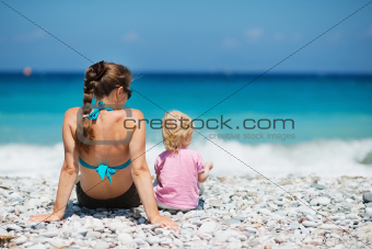 Mother sitting with baby on beach. Rear view