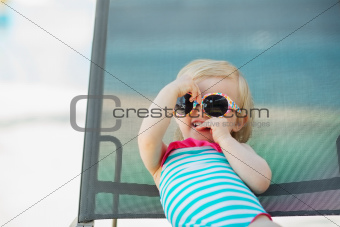 Portrait of baby in swimsuit and sunglasses laying on sunbed