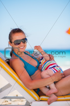 Mother laying on sunbed and holding baby drinking water