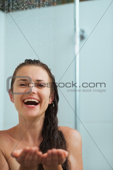 Happy woman catching water drops in shower under water jet