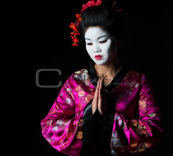 Portrait of geisha with hands together respect gesture isolated on black