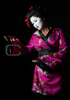 Portrait of geisha presenting something isolated on black