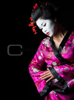 Closeup portrait of geisha isolated on black