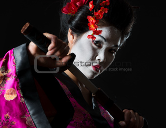 Portrait of geisha pulls out sword of sheath on black