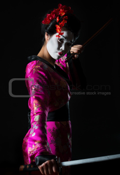 Portrait of geisha holding sword isolated on black
