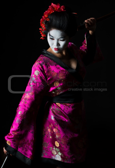 Portrait of geisha dancing with sword isolated on black
