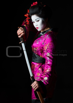 Portrait of geisha warrior pulls out sword of sheath on black