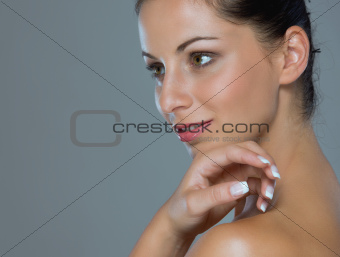 Beauty portrait of girl showing well-groomed hands on gray