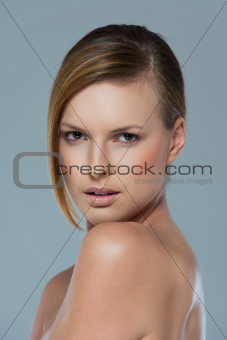 Beauty portrait of serous girl isolated on gray