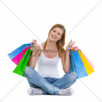 Full length portrait of smiling teenage girl sitting with shopping bags