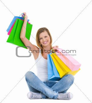 Full length portrait of happy teenage girl sitting with shopping bags