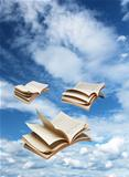 Three open books flying on blue sky