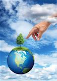 Hand reaching planet Earth